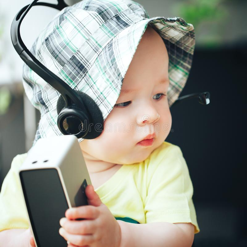 Ragazzo infantile del bambino del bambino sei mesi con l'altoparlante e le cuffie sani immagine stock libera da diritti