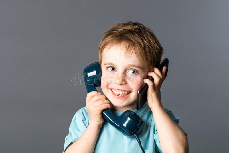 Ragazzo insolente che parla su entrambe le orecchie per una comunicazione vocale due immagini stock libere da diritti