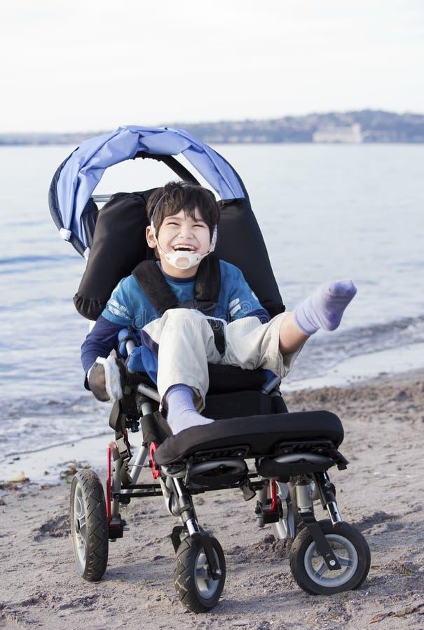 Ragazzo invalido felice in sedia a rotelle sulla spiaggia fotografia stock libera da diritti