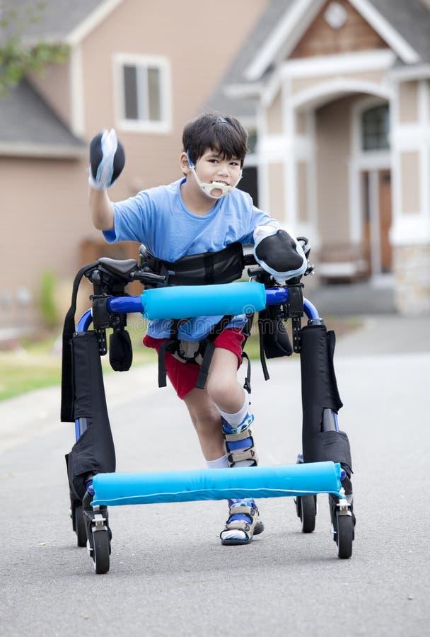 Ragazzo invalido sei anni in camminatore sulla via fotografia stock