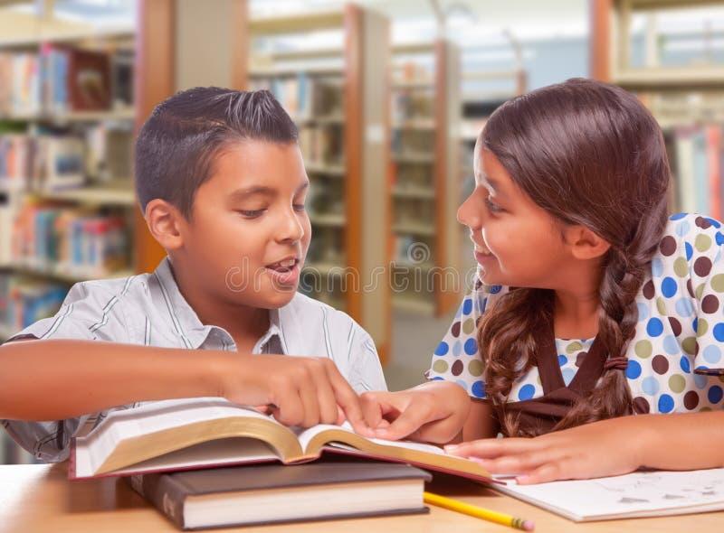 Ragazzo ispano e ragazza divertendosi studio insieme nella biblioteca fotografia stock libera da diritti