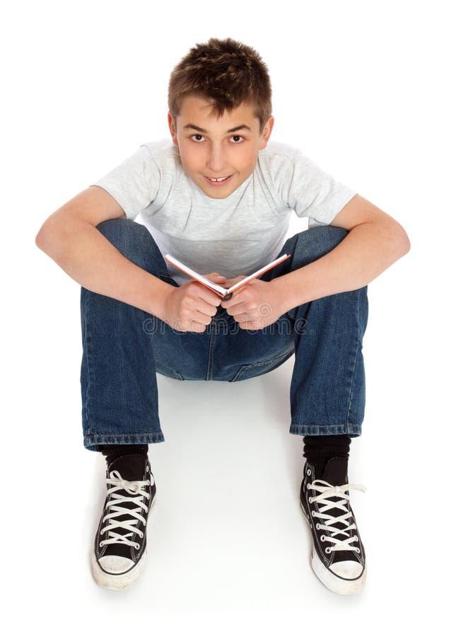 Ragazzo in jeans che si siedono sul pavimento fotografia stock libera da diritti