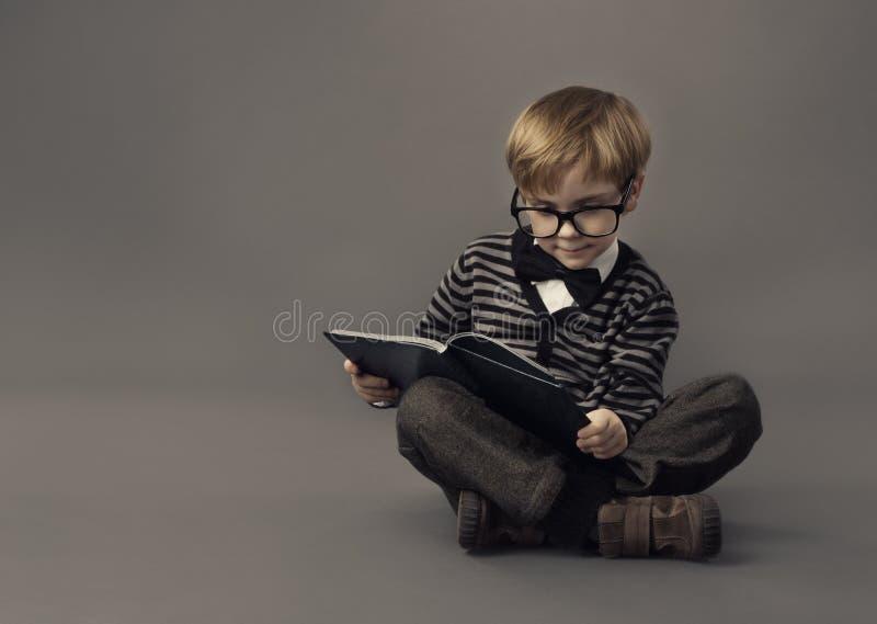 Ragazzo in libro di lettura di vetro, st astuta del piccolo bambino immagine stock libera da diritti