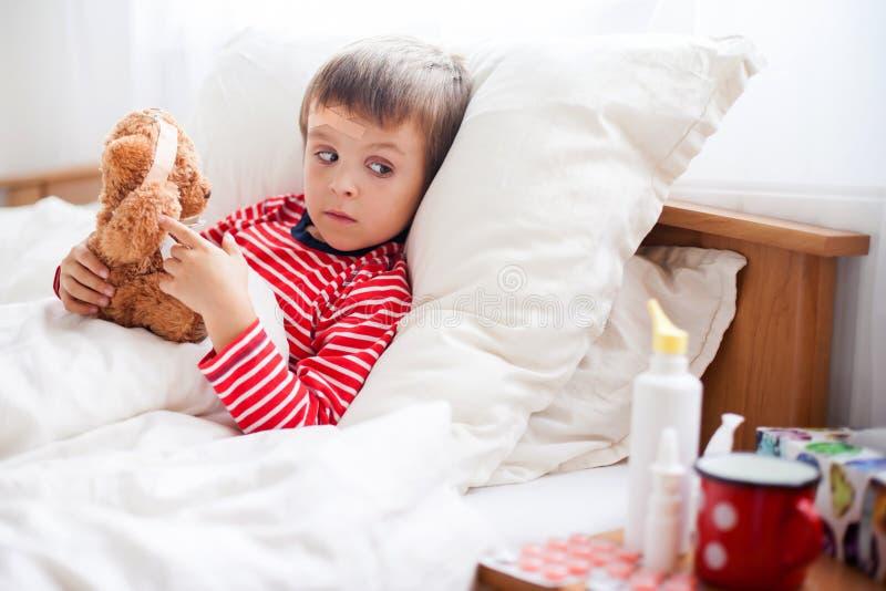 Ragazzo malato del bambino che si trova a letto con una febbre, riposante immagine stock