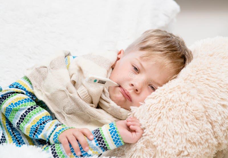 Ragazzo malato triste con il termometro che si situa a letto immagini stock
