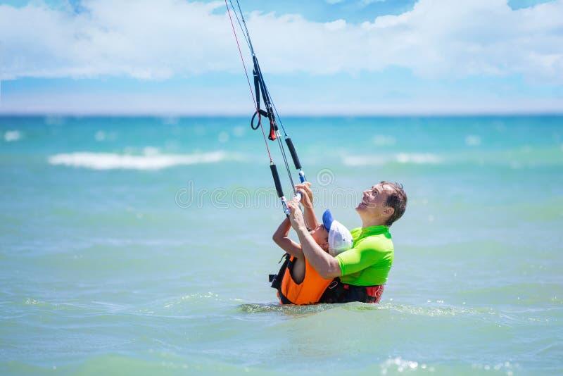 Ragazzo maschio del surfista dell'aquilone a giovane insegnando a come guidare aquilone immagine stock libera da diritti