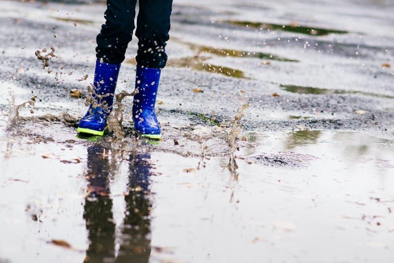Ragazzo nei rainboots blu di gomma che saltano alla pozza sporca fotografie stock