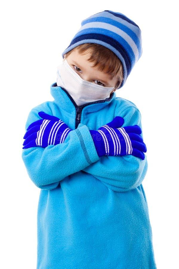Ragazzo nei vestiti di inverno e nella mascherina medica immagine stock