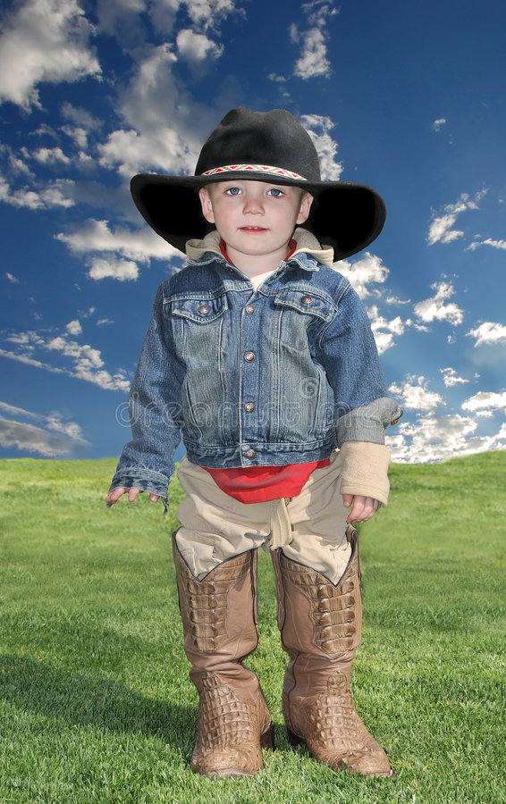 Ragazzo nel cappello e nei caricamenti del sistema del cowboy fotografia stock libera da diritti