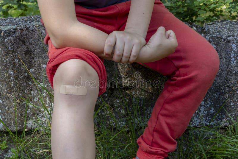 Ragazzo nel dolore con la fasciatura sul suo ginocchio immagini stock libere da diritti
