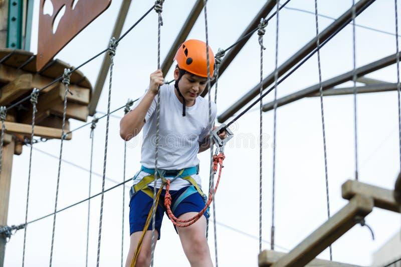 Ragazzo nel parco di avventura della foresta Bambino in casco arancio e salite bianche della maglietta sull'alta traccia della co immagine stock