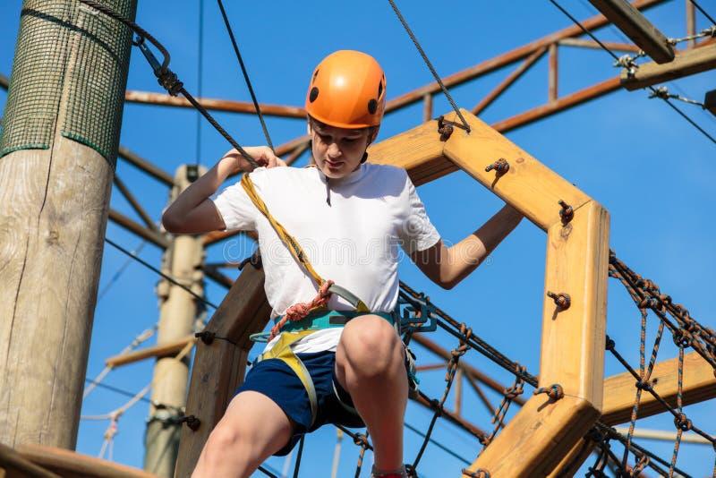 Ragazzo nel parco di avventura della foresta Bambino in casco arancio e salite bianche della maglietta sull'alta traccia della co fotografie stock