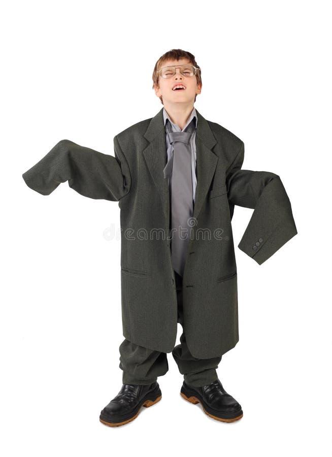 Ragazzo nel vestito del grande uomo, in caricamenti del sistema e nel pavimento di vetro fotografia stock libera da diritti