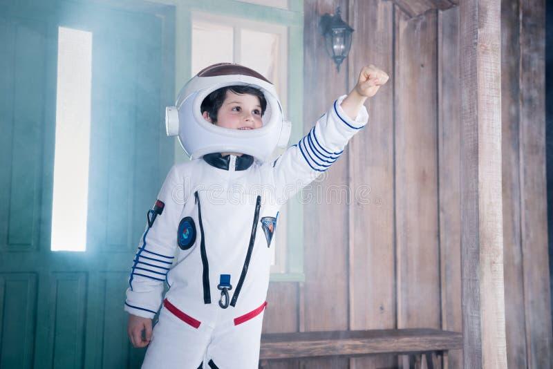 Ragazzo nel volo del costume dell'astronauta sul portico immagine stock
