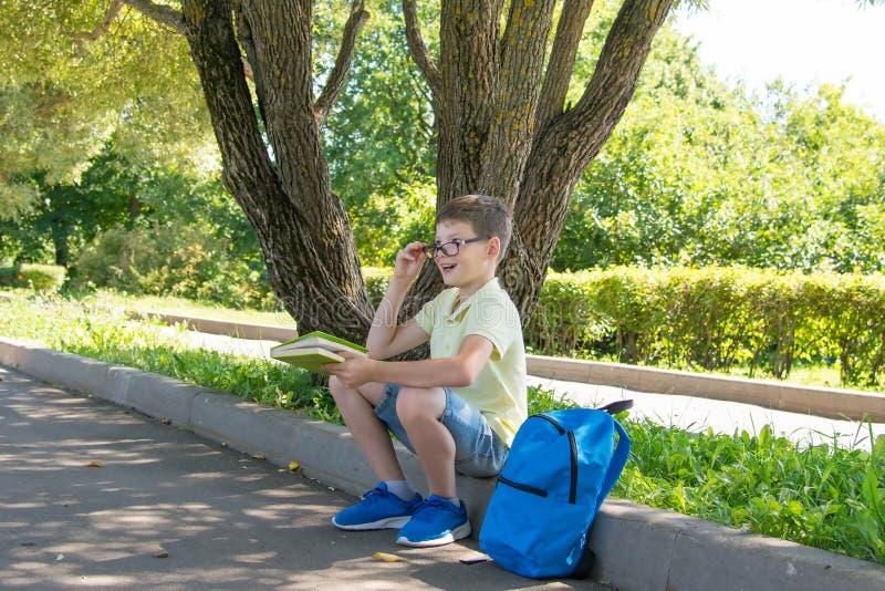 Ragazzo nella via che legge un libro e che esprime le emozioni circa cui ha letto, alzando i suoi vetri su fotografia stock