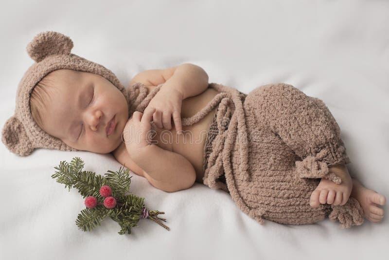 Ragazzo neonato addormentato in un costume divertente dell'orso fotografie stock