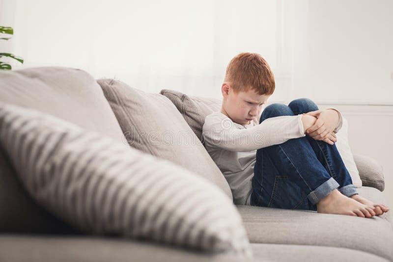 Ragazzo offensivo che si siede sul sofà a casa fotografie stock