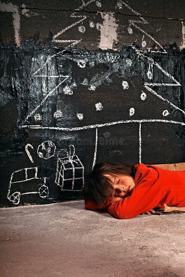 Ragazzo povero che sogna dei regali di Natale immagine stock libera da diritti