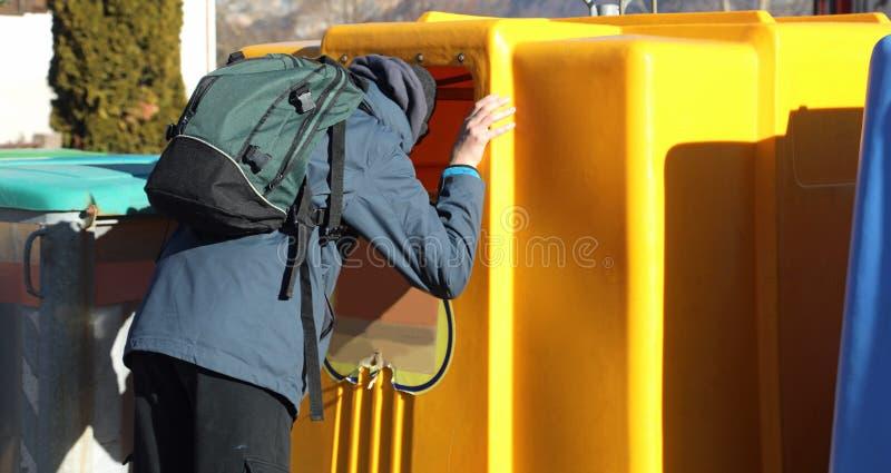 Ragazzo povero con uno zaino che cerca nel recipiente dei rifiuti il someth fotografia stock