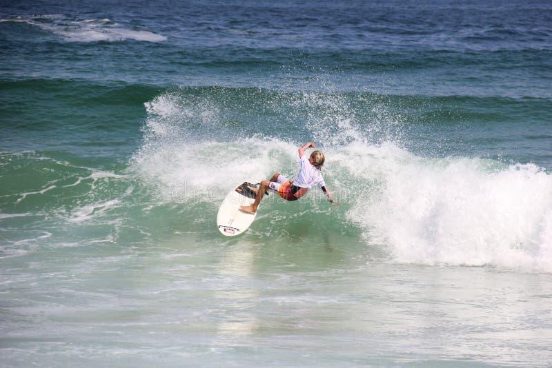 Ragazzo praticante il surfing alla spiaggia di Arpoador in Rio de Janeiro fotografia stock libera da diritti