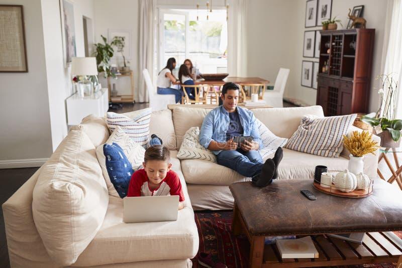 Ragazzo Pre-teen che si trova sul sofà facendo uso del computer portatile, del papà che utilizzano compressa, della mummia, della fotografia stock libera da diritti