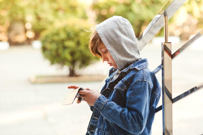 Ragazzo Preteen che gioca sullo smartphone all'aperto Svago, bambini, tecnologia, comunicazione di Internet e concetto della gent fotografia stock libera da diritti