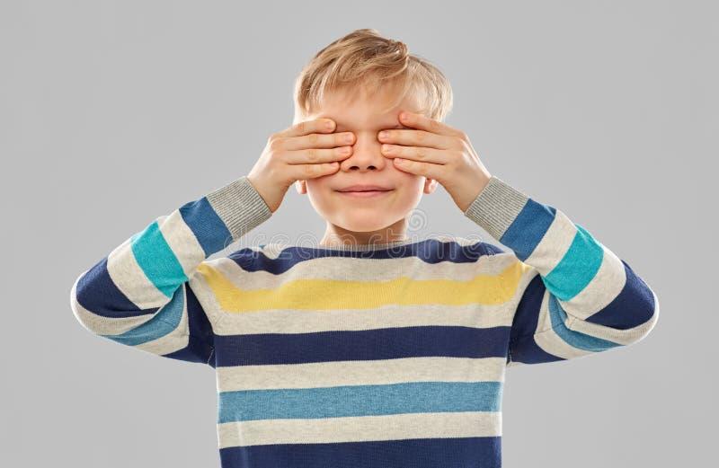 Ragazzo in pullover a strisce che chiude i suoi occhi a mano immagini stock