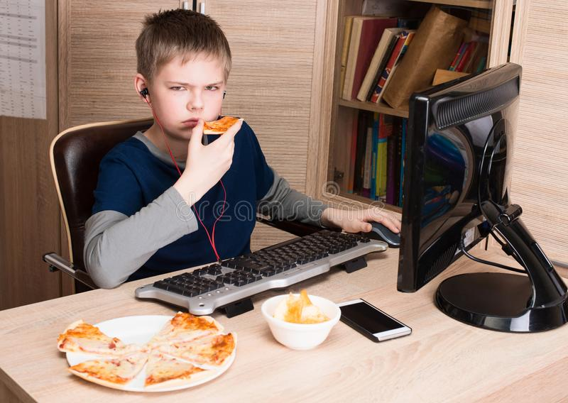 Ragazzo scontroso e dispiaciuto che mangia pizza e che pratica il surfing su Internet sulla P immagini stock libere da diritti