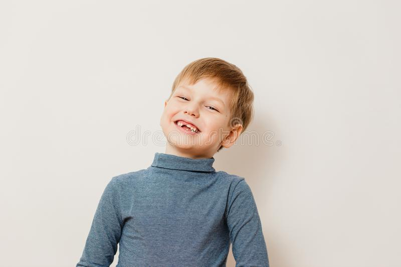 Ragazzo senza denti allegro sei anni in collo alto a strisce su fondo bianco fotografia stock libera da diritti