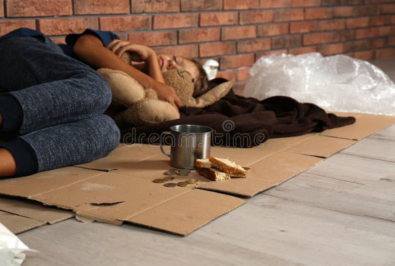 Ragazzo senza tetto povero che dorme con il suo giocattolo sul pavimento immagine stock libera da diritti