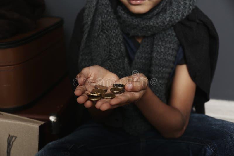 Ragazzo senza tetto povero con la supplica delle monete fotografia stock