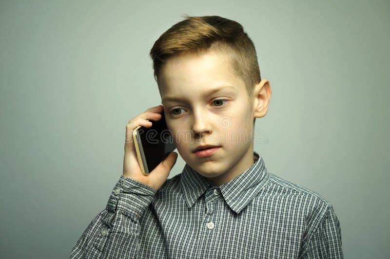 Ragazzo serio adolescente con taglio di capelli alla moda che parla sullo smartphone fotografia stock