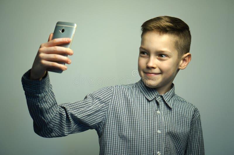 Ragazzo serio adolescente con taglio di capelli alla moda che prende selfie sullo smartphone immagini stock