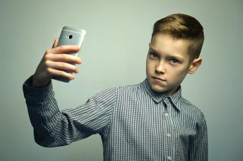 Ragazzo serio adolescente con taglio di capelli alla moda che prende selfie sullo smartphone immagine stock