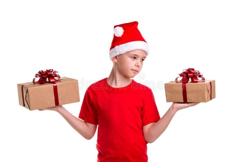 Ragazzo serio bello, cappello di Santa sulla sua testa, con due contenitori di regalo sulle mani, guardanti a sinistra scatola Co fotografia stock libera da diritti