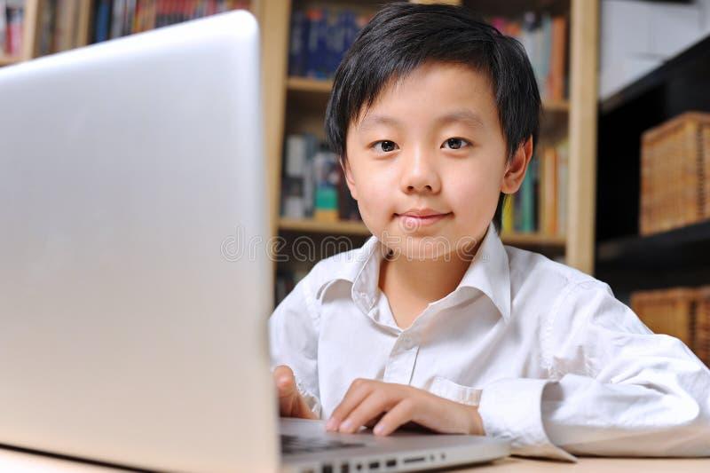 Ragazzo sicuro in camicia bianca davanti al computer portatile fotografia stock
