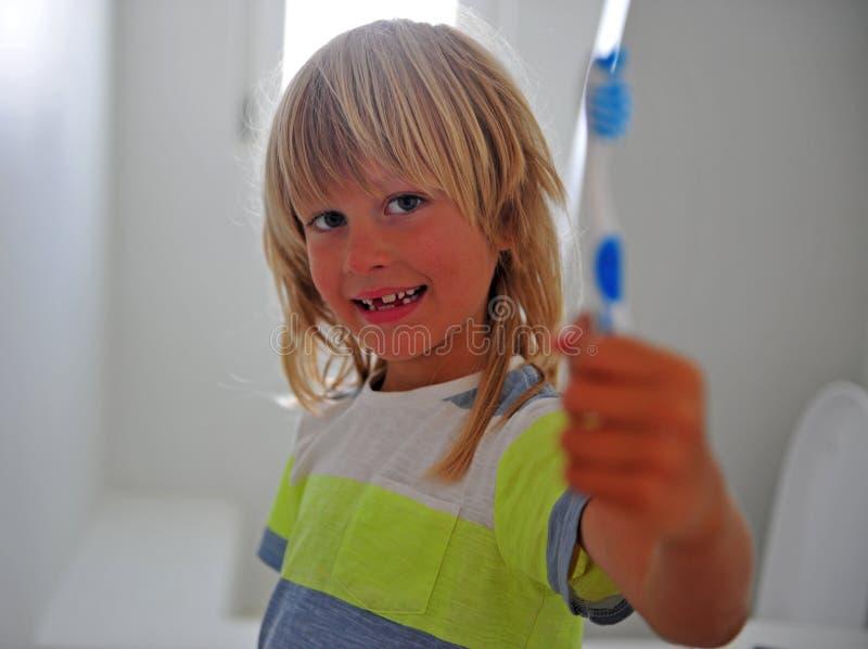Ragazzo sorridente allegro con uno spazzolino da denti nel bagno fotografia stock