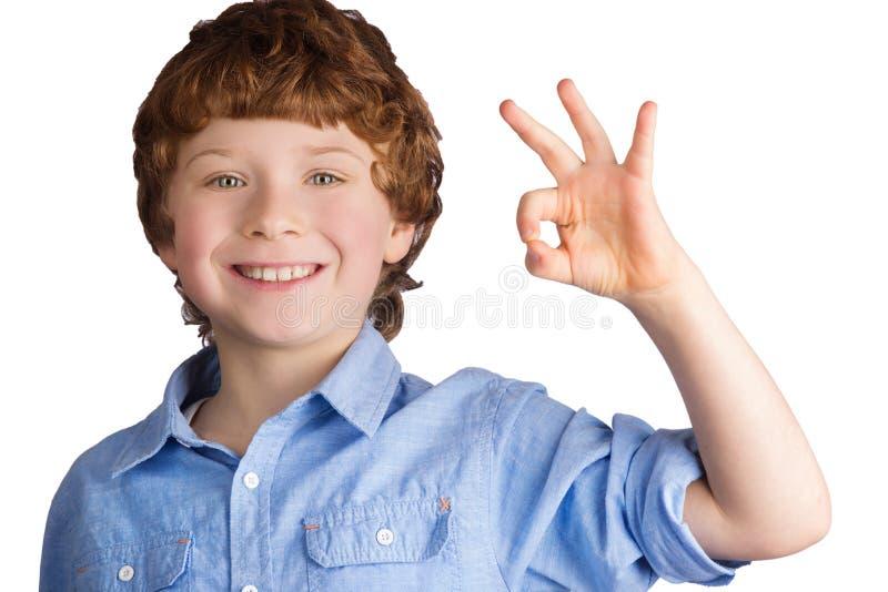 Ragazzo sorridente bello che mostra segno GIUSTO con la sua mano fotografia stock