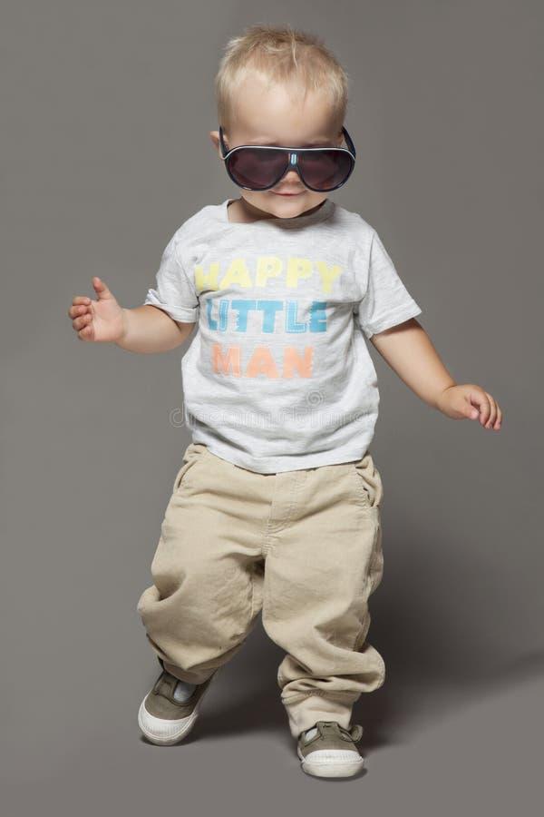 Ragazzo sorridente biondo del bambino di bellezza in occhiali da sole fotografia stock