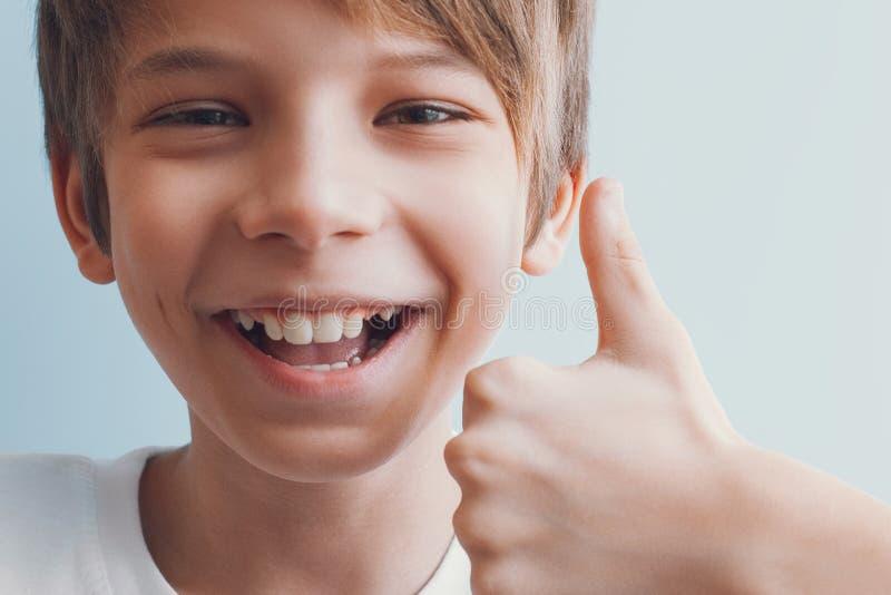 Ragazzo sorridente che mostra i pollici su Concetto di emozione fotografie stock