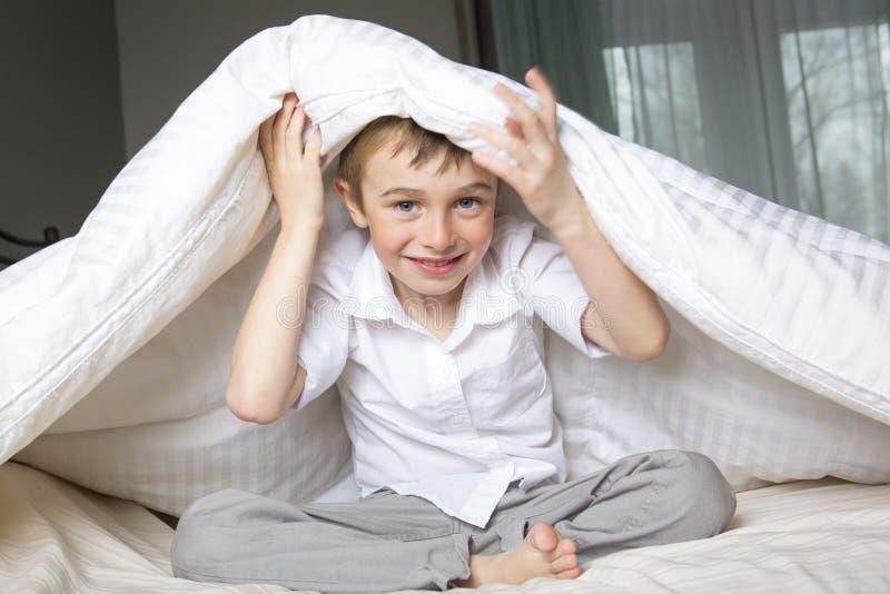 Ragazzo sorridente che si nasconde a letto sotto una coperta o un copriletto bianca fotografia stock libera da diritti