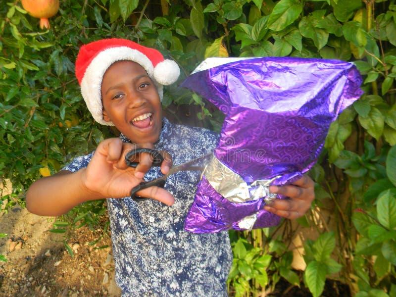 Ragazzo sorridente con il presente di apertura del cappello di Christmas del padre immagini stock libere da diritti