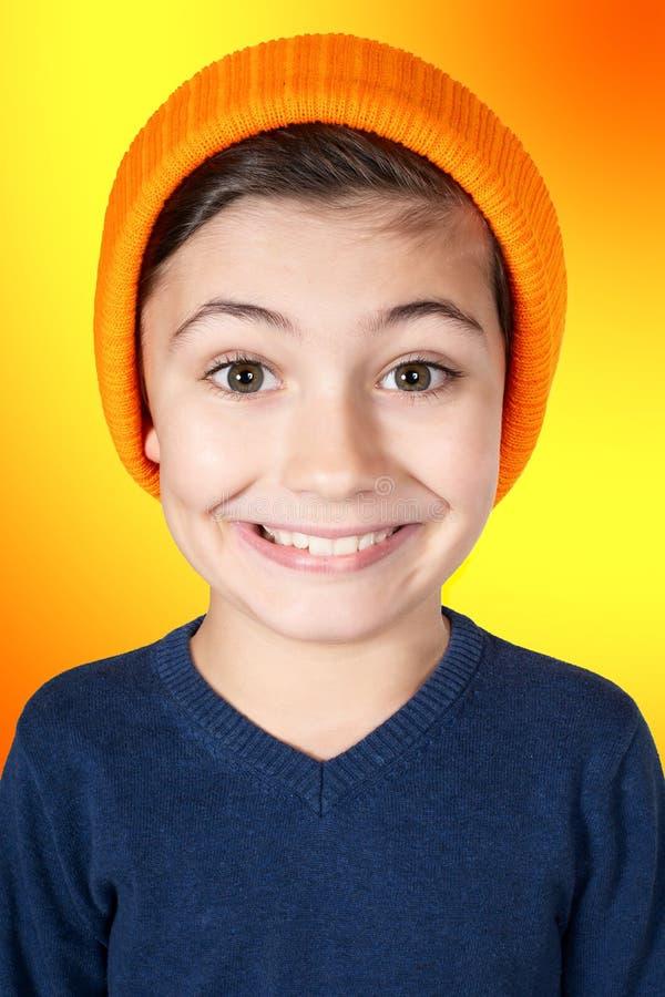 Ragazzo sorridente con la grande testa ed il fondo arancio immagine stock libera da diritti