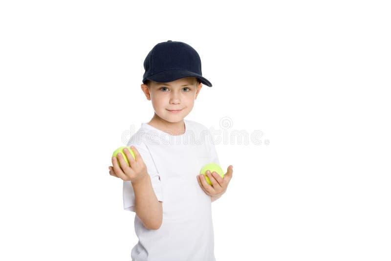 Ragazzo sorridente con le sfere di tennis fotografie stock libere da diritti