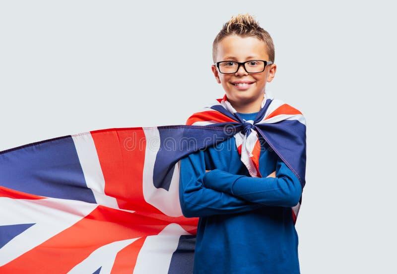 Ragazzo sorridente del supereroe con il capo della bandiera di Britannici immagini stock