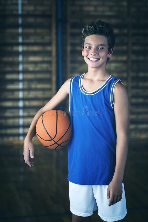 Ragazzo sorridente della High School che tiene una pallacanestro nella corte immagine stock libera da diritti