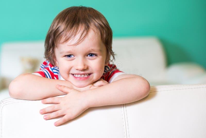Ragazzo sorridente felice del piccolo bambino che si siede su un sofà fotografie stock