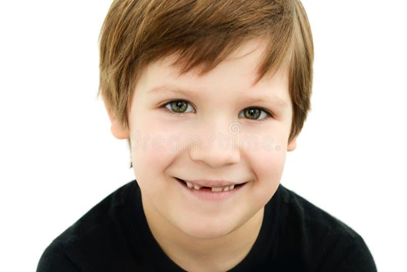 Ragazzo sorridente senza un dente da latte su un fondo bianco immagini stock libere da diritti