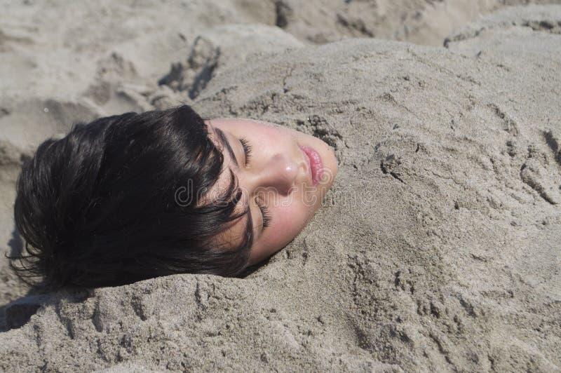 Ragazzo sotto la sabbia immagine stock libera da diritti