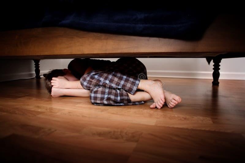 Ragazzo spaventoso che si nasconde sotto il letto immagini stock